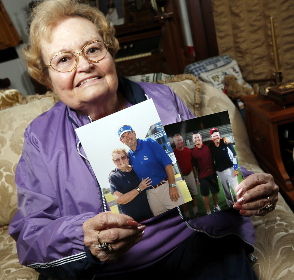 Photo - Gay Gower poses for a photo with a picture of her with her son Grant Gower, head football coach at Deer Creek, as well as a photo of her son Andy Gower, a former football coach, left,  her grandson Ty Gower, an assistant coach at Broken Arrow, and son Grant Gower, at her home in Tecumseh, Okla., Wednesday, Nov. 14, 2012. Photo by Nate Billings, The Oklahoman