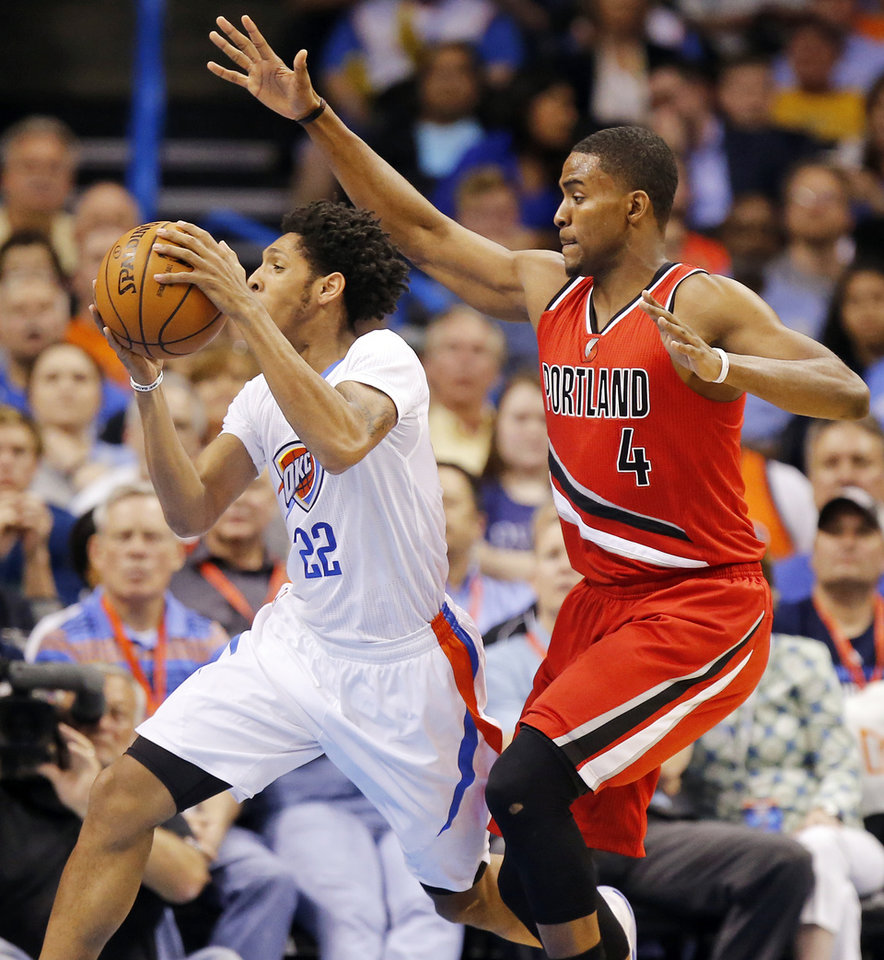 Photo - Oklahoma City's Cameron Payne, left, takes the ball past Portland's Maurice Harkless during Monday's game between the Thunder and Portland Trail Blazers at Chesapeake Energy Arena, Oklahoma City won 128-94. (Photo by Nate Billings, The Oklahoman)