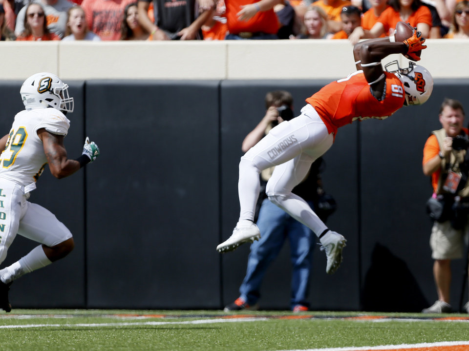 Photo - Oklahoma State's Jhajuan Seales (81) makes a leaping catch for a touchdown in front of Courtney Rutledge (29) in the first quarter during the college football game between the Oklahoma State Cowboys (OSU) and the Southeastern Louisiana Lions at Boone Pickens Stadium in Stillwater, Okla., Saturday, Sept. 12, 2015. Photo by Sarah Phipps, The Oklahoman
