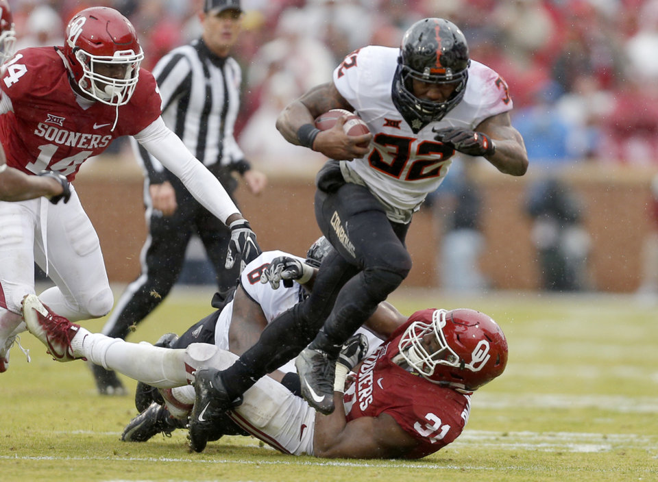 Photo - Oklahoma State's Chris Carson (32) rushes as Oklahoma's Ogbonnia Okoronkwo (31) defends during the Bedlam college football game between the Oklahoma Sooners (OU) and the Oklahoma State Cowboys (OSU) at Gaylord Family - Oklahoma Memorial Stadium in Norman, Okla., Saturday, Dec. 3, 2016. OU won 38-20. Photo by Sarah Phipps, The Oklahoman