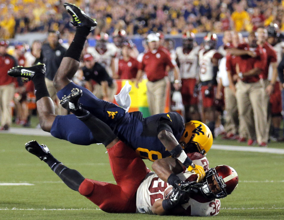Photo - Oklahoma's Samaje Perine (32) is tackled by West Virginia's Karl Joseph (8) during the college football game between West Virginia  Mountaineers and the University of Oklahoma Sooners at Milan Puskar Stadium in Morgantown, W.Va., Saturday, Sept. 20, 2014. Photo by Sarah Phipps, The Oklahoman