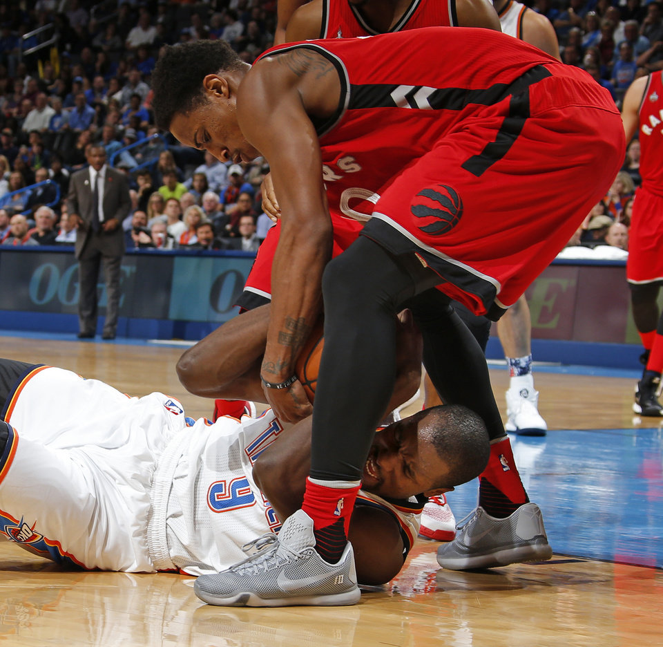 Photo - Oklahoma City's Serge Ibaka (9) fights for a loose ball with Toronto's DeMar DeRozan (10) during an NBA basketball game between the Oklahoma City Thunder and the Toronto Raptors at Chesapeake Energy Arena on Wednesday, Nov. 4, 2015. The Thunder lost 103-98. Photo by Bryan Terry, The Oklahoman