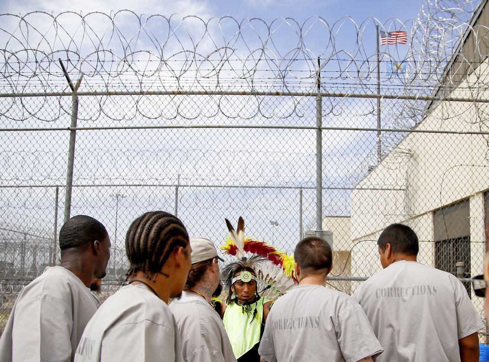 Photo - Micco Pohlemann, a Kiowa and Seminole, talks with other inmates during the 27th Annual Confined Inter-Tribal Group Gourd Dance & Pow-Wow inside Joseph Harp Correctional Center in Lexington, Okla., on Friday, September 9, 2016. Photo by Bryan Terry, The Oklahoman