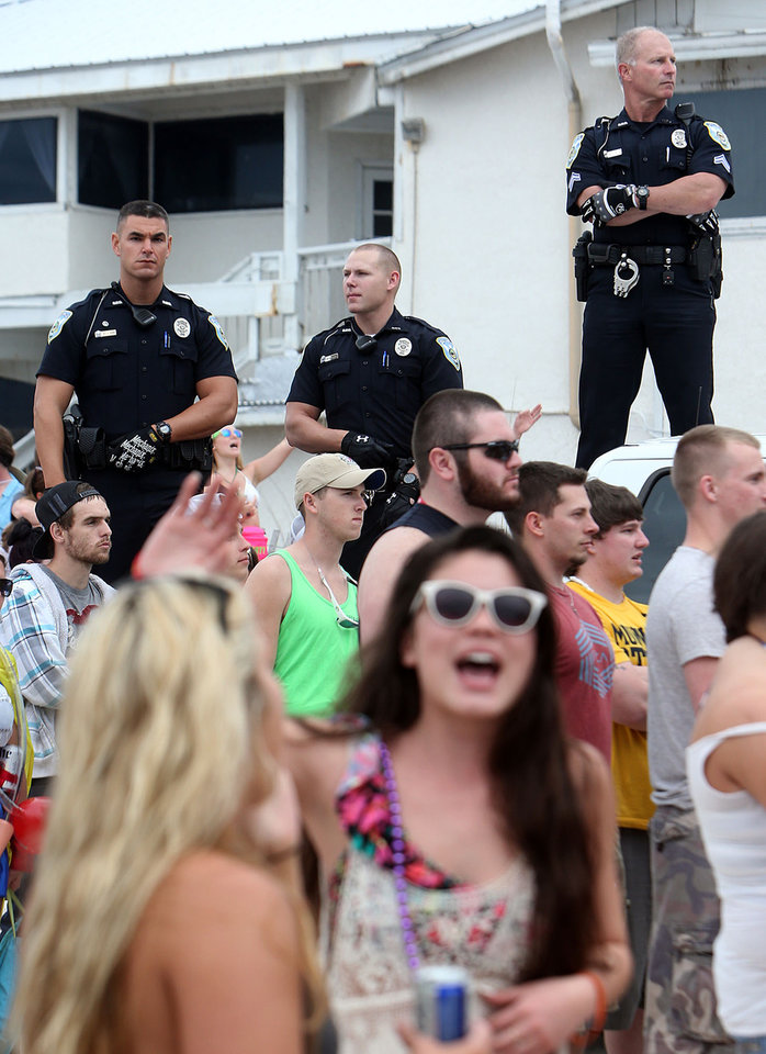 Photo - FILE - This March 11, 2014 file photo shows Panama City Beach Police Officers watching over a large crowd of spring breakers during a Luke Bryan concert in Panama City, Fla. (AP Photo/The News Herald/Panama City, Fla., Andrew Wardlow)