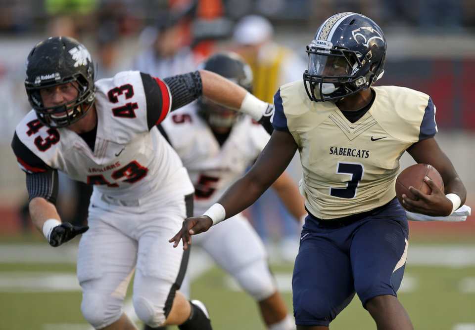 Photo - Southmoore's Jaleon Walker goes past Westmoore's Jacob Tilley during their high school football game in Moore, Okla., Friday, Sept. 13, 2013. Photo by Bryan Terry, The Oklahoman