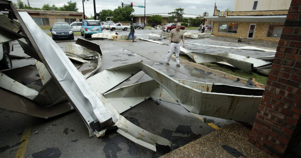 Above: The roof of a strip mall at Gray Street and Webster Avenue lies in a parking lot on April 13 after a tornado forged a path through Norman.