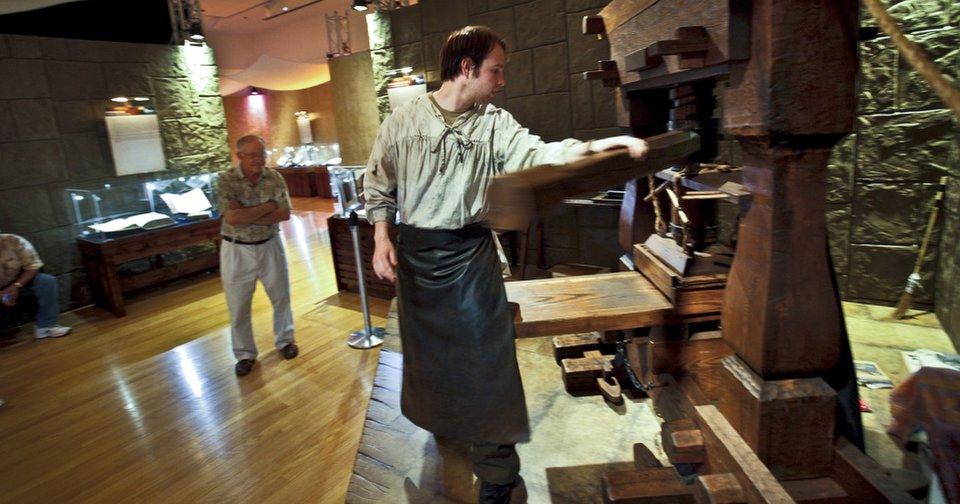 """Andrew Cole demonstrates the operations of a Gutenberg press to visitors of the """"Passages"""" exhibit at the Oklahoma City Museum of Art. The collection of biblical artifacts was on display last year. Photos by Chris Landsberger, The Oklahoman Archives"""