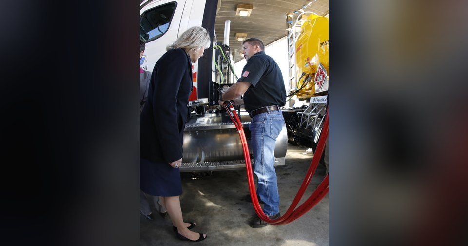 Gov. Mary Fallin, left, watches as Gemini Motor Transport driver Robert Felts demonstrate how to fill his truck with compressed natural gas.