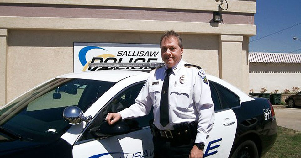 Sallisaw Police Chief Shaloa Edwards stands next to his police car in this photo from his Facebook page. Edwards has been stripped of his supervisory powers amid an investigation.