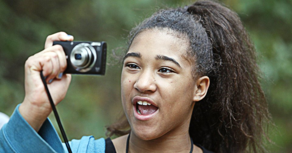 Katyra, 10, takes photos during an outing with The Boys and Girls Club\'s new program called