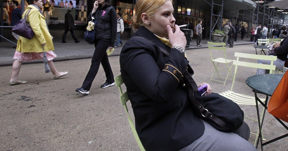 Amanda Perez smokes a cigarette in New York's Herald Square. Monday, a new law went into effect banning smoking in New York City's urban parks and other public places. The law will be enforced with a $50 fine per violation.AP Photo