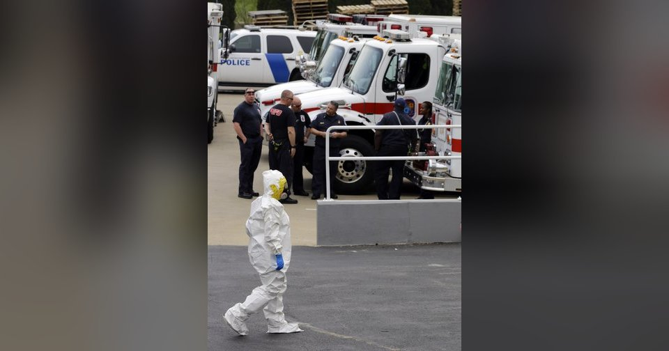 A Prince George's County, Md., firefighter dressed in a protective suit walks past emergency personnel into a government mail screening facility. AP Photo