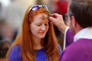 A woman approaches the altar to have a cross traced on her forehead with blessed ashes by Deacon Marti Guilikers during a noon Ash Wednesday service at St. James the Greater Catholic Church, 4201 S McKinley. [Photo by Jim Beckel, The Oklahoman]