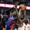 Detroit Pistons center Greg Monroe (10) shoots against Chicago Bulls guard Kirk Hinrich, left, forward Luol Deng (9) and guard Jimmy Butler during the first half of an NBA basketball game in Chicago, Sunday, March 31, 2013. (AP Photo/Nam Y. Huh)