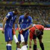 Photo - Italy's Giorgio Chiellini, left, and Claudio Marchisio, center, assist England's Raheem Sterling to stretch during the group D World Cup soccer match between England and Italy at the Arena da Amazonia in Manaus, Brazil, Saturday, June 14, 2014. (AP Photo/Martin Mejia)