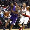 Photo - Sacramento Kings guard Aaron Brooks, left, drives the baseline against Portland Trail Blazers guard Damian Lillard during the first quarter of their NBA basketball game in Portland, Ore., Saturday, Dec. 8, 2012.(AP Photo/Don Ryan)