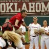 "Photo - Jim Routon, Moore tornado survivor and ""Big Dog"" in a photograph by Paul Hellstern that appeared following the deadly tornado, threw out the first pitch and celebrated with a scissor kick before the University of Oklahoma Sooner (OU) softball team plays Tennessee in the first game of the NCAA super regional at Marita Hynes Field on May 23, 2014 in Norman, Okla. Photo by Steve Sisney, The Oklahoman"