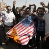 Followers of Shiite cleric Muqtada al-Sadr burn the U.S. flag during a demonstration as part of widespread anger across the Muslim world about a film ridiculing Islam\'s Prophet Muhammad, in Baghdad, Iraq, Thursday, Sept. 13, 2012. Hundreds of followers of the anti-American Shiite cleric Muqtada al-Sadr demanded the closure of the U.S. Embassy in Baghdad because of the film. (AP Photo/Karim Kadim) ORG XMIT: BAG110