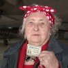 """Photo - In this April 15, 2014, image from video, Loraine Osborne, a former """"Rosie the Riveter"""" who worked at the Willow Run bomber plant, holds up her old Ford Motor Co. identification card at the plant in Ypsilanti Township, Mich. A group wants to preserve a portion of the plant and house a museum there dedicated to aviation and the countless Rosies across the country. Save the Bomber Plant officials have until Thursday, May 1, to raise the remainder of the $8 million needed to save the plant from demolition. (AP Photo, Mike Householder)"""