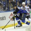St. Louis Blues\' Jay Bouwmeester, left, and Chicago Blackhawks\' Jonathan Toews, right, battle for the puck during the first period in Game 2 of a first-round NHL hockey playoff series on Saturday, April 19, 2014, in St. Louis. (AP Photo/Bill Boyce)