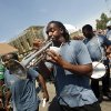 Photo - FILE - In this Aug. 29, 2011 file photo, a member of the Big 9 marching club plays trumpet in a second line  commemorating the sixth anniversary of Hurricane Katrina in New Orleans. New Orleans officials and cultural advocates say the Mother's Day parade shootings that left 20 people injured won't spell the end of second-line parades, the local tradition that celebrates the city and its people. (AP Photo/Gerald Herbert, File)