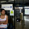 Photo - A woman stands outside a closed United Airlines office in Caracas, Venezuela, Friday, Jan. 24, 2014.  Delta, American Airlines and Panama's Copa Airlines were also among carriers whose offices were either closed or had halted sales on Friday after the government devalued the local currency for flights abroad. (AP Photo/Alejandro Cegarra)