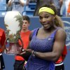 Photo - Serena Williams poses with the championship trophy after defeating Ana Ivanovic, from Serbia, 6-4, 6-1, in a final match at the Western & Southern Open tennis tournament, Sunday, Aug. 17, 2014, in Mason, Ohio. (AP Photo/Al Behrman)