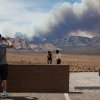 A family visiting the Red Rock Canyon National Conservation Area takes photos as smoke from the Carpenter 1 fire rises over Mount Charleston near Las Vegas on Tuesday, July 9, 2013. The fire which started by lightning-strike on July 1 is only fifteen percent contained. (AP Photo/Las Vegas Review-Journal, Chase Stevens)