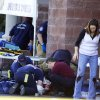 Photo - FILE - In this Jan. 8, 2011 file photo, emergency personnel attend to a shooting victim outside a shopping center in Tucson, Ariz., where U.S. Rep. Gabrielle Giffords, D-Ariz., and others were shot as the congresswoman was meeting with constituents. Hundreds of pages of police reports in the investigation of the Tucson shooting rampage that wounded former Rep. Gabrielle Giffords were released Wednesday, March 27, 2013 marking the public's first glimpse into documents that authorities have kept private since the attack more than two years ago.  (AP Photo/James Palka, File)