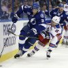Tampa Bay Lightning defenseman Keith Aulie (3) carries the puck past New York Rangers center Brad Richards (19) during the first period of an NHL hockey game on Saturday, Feb. 2, 2013, in Tampa, Fla. (AP Photo/Chris O\'Meara)