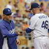 Photo - Los Angeles Dodgers bench coach Tim Wallach, left, takes the ball from starting pitcher Paul Maholm in the third inning of a spring exhibition baseball game against the Cincinnati Reds, Thursday, March 13, 2014, in Glendale, Ariz. Wallach was acting manager for the game. (AP Photo/Mark Duncan)