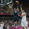 Photo -   USA's Andre Iguodala (9) towers over Tunisia's Mohamed Hadidane as he slam dunks during a men's basketball game at the 2012 Summer Olympics, Tuesday, July 31, 2012, in London. (AP Photo/Charles Krupa)