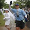 Joel Rogalsky and Amy Wills wave to the crowd as they stop to get married during the Oklahoma City Memorial Marathon on NW 35th, Sunday, May 1, 2011. Photo by Bryan Terry, The Oklahoman