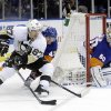 Photo - New York Islanders' Andrew MacDonald (47) defends Pittsburgh Penguins' Sidney Crosby (87) as he looks to pass away from goalie Kevin Poulin (60) during the first period of an NHL hockey game, Thursday, Jan. 23, 2014 in Uniondale, N.Y. (AP Photo/Frank Franklin II)