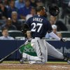 Milwaukee Brewers center fielder Carlos Gomez loses his helmet as he swings and misses in the seventh inning of a baseball game against Atlanta Braves, Monday, May 19, 2014 in Atlanta. (AP Photo/John Bazemore)