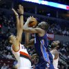 Charlotte Bobcats\' Bismack Biyombo (0) shoots against Portland Trail Blazers\' Nicolas Batum (88) and JJ Hickson (21) during the first half of an NBA basketball game in Portland, Ore., Monday, March 4, 2013. (AP Photo/Greg Wahl-Stephens)