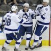 Photo - Tampa Bay Lightning right wing Martin St. Louis, center, celebrates scoring a goal with teammates Ondrej Palat (18) and Eric Brewer (2) during the first period of an NHL hockey game against the Dallas Stars Saturday, March 1, 2014, in Dallas. (AP Photo/LM Otero)