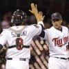 Photo - Minnesota Twins relief pitcher Anthony Swarzak (51) is congratulated by teammate Kurt Suzuki (8) after they beat the Kansas City Royals 10-1 in a baseball game, Friday, April 11, 2014, in Minneapolis. AP Photo/Paul Battaglia)