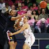 Photo -   West Virginia center Ayana Dunning, left, throws a pass around Notre Dame guard Kayla McBride during the first half of an NCAA college basketball game, Sunday, Feb. 12, 2012, in South Bend, Ind. (AP Photo/Joe Raymond)