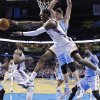 Photo - Oklahoma City Thunder guard Reggie Jackson (15) passes from under the basket in front of Denver Nuggets center Timofey Mozqov (25) in the first quarter of an NBA basketball game in Oklahoma City, Monday, March 24, 2014. (AP Photo/Sue Ogrocki)