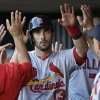 Photo - St. Louis Cardinals' Matt Carpenter (13) is congratulated in the dugout after scoring on a hit by Allen Craig in the fourth inning of a baseball game against the Cincinnati Reds, Friday, May 23, 2014, in Cincinnati. (AP Photo/Al Behrman)