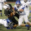 Putnam City\'s Braden Hudson is brought down by Sapulpa\'s Tanner Gregory (42) and Jacob Shanahan (13) during their high school football game at Putnam City in Oklahoma City, Thursday, Sept. 26, 2013. Photo by Bryan Terry, The Oklahoman
