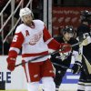 Photo - Pittsburgh Penguins' Lee Stempniak, right, heads for the bench following his second-period goal as Detroit Red Wings' Niklas Kronwall (55), of Sweden, left, skates away during an NHL hockey game Thursday, March 20, 2014, in Detroit. (AP Photo/Duane Burleson)