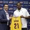 Photo - Cleveland Cavaliers general manager Chris Grant, left, and Andrew Bynum hold up Bynum's No. 21 jersey during an NBA basketball news conference on Friday, July 19, 2013, in Independence, Ohio. Bynum was introduced after agreeing to terms on a two-year contract with the Cavaliers. (AP Photo/Tony Dejak)