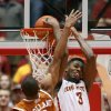 Photo - Iowa State forward Melvin Ejim scores on a reverse dunk against Texas' Demarcus Holland during the second half of an NCAA college basketball game in Ames, Iowa, Tuesday, Feb. 18, 2014. Ejim led Iowa State with 25 points in the team's 85-76 victory. (AP Photo/Justin Hayworth)