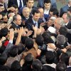 Photo - In this photo released by the Syrian official news agency SANA, Syrian President Bashar Assad, center, greets his supporters after he attended prayers on the first day of Eid al-Adha, at the Sayeda Hassiba mosque, in Damascus, Syria, Tuesday, Oct. 15, 2013. (AP Photo/SANA)
