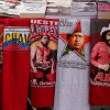 Iconic T-shirts styled with images of Venezuela\'s President Hugo Chavez are displayed for sale next to a T-shirt of Venezuelan musician Ali Primera, in Caracas, Venezuela, Friday, Dec. 28, 2012. The obsessive, circular conversations about Chavez\'s health dominate family dinners, plaza chit-chats and social media sites in this country on edge since its larger-than-life leader went to Cuba for emergency cancer surgery more than two weeks ago. The man whose booming voice once dominated the airwaves for hours at a time has not been seen or heard from since.(AP Photo/Fernando Llano)