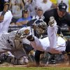 Photo - Pittsburgh Pirates' Starling Marte, right, slides into the tag by Colorado Rockies catcher Wilin Rosario, center, as umpire Tim Timmons watches during the fifth inning of a baseball game in Pittsburgh on Friday, July 18, 2014. Marte attempted to stretch a triple into an inside-the-park home run and was out at the plate, but not before driving in Gregory Polanco with the Pirates' first run. (AP Photo/Gene J. Puskar)