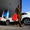 Photo -  A man carries a fuel tank for gasoline Thursday at a gas station in Irbil, Iraq. The Iraqi military appeared to be holding on after three days of battle against Sunni militants for control of Iraq's largest oil refinery. AP Photo  <strong>Uncredited -   </strong>