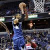 Minnesota Timberwolves forward Chris Johnson, top, goes to the basket against Washington Wizards center Nene, right, of Brazil, during the first half of an NBA basketball game on Friday, Jan. 25, 2013, in Washington. (AP Photo/Nick Wass)